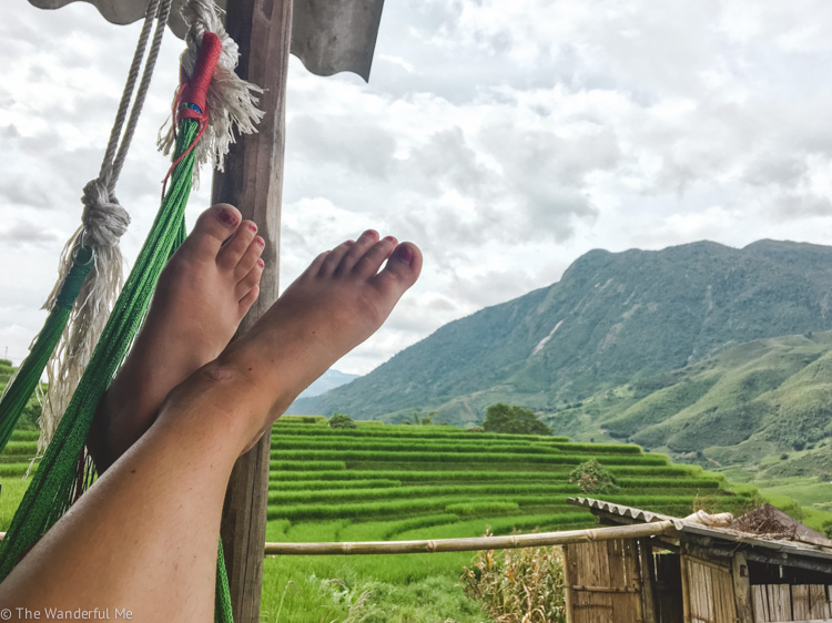 Sophie sitting in a hammock with her feet up and a gorgeous view of ridiculously green rice fields.