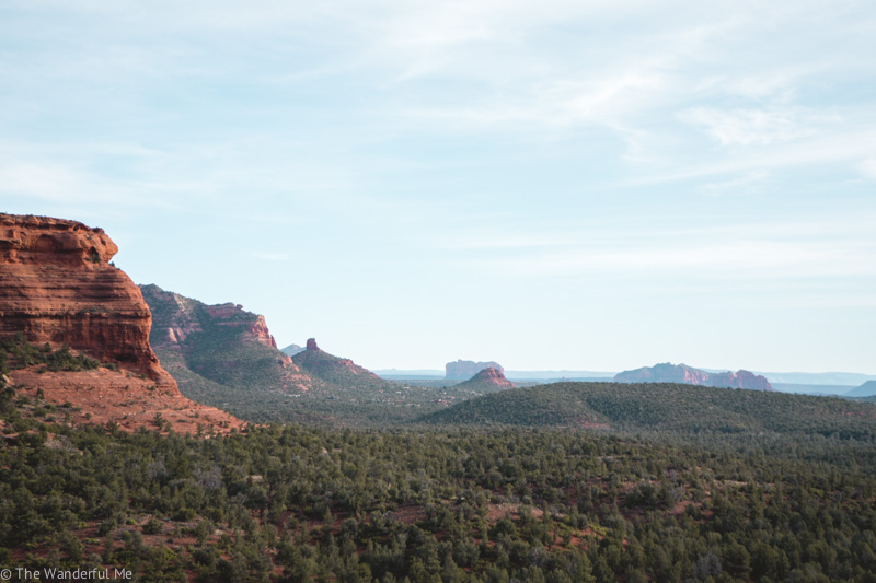 Views overlooking the Sedona valley, featuring green trees, blue mountains, and gorgeous red rocks.