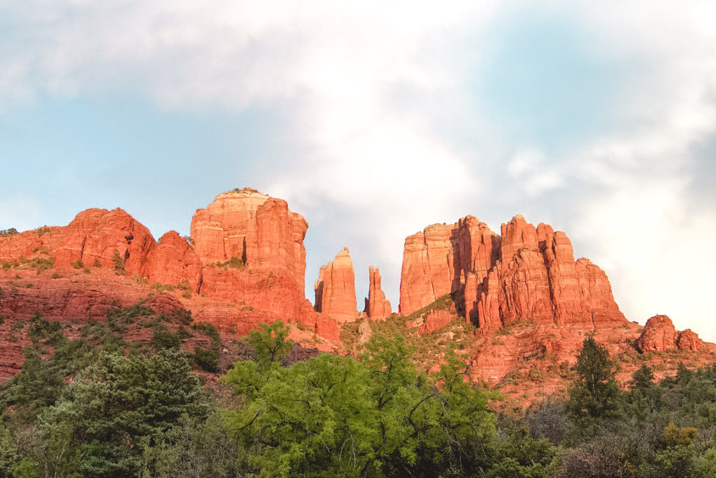 The views of Cathedral Rock with the sunlight hitting the red rock, lighting it up as though it's on fire.