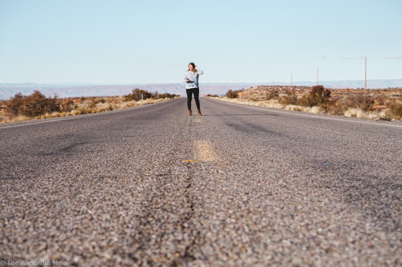 Sophie standing in the middle of the road somewhere in the desert.
