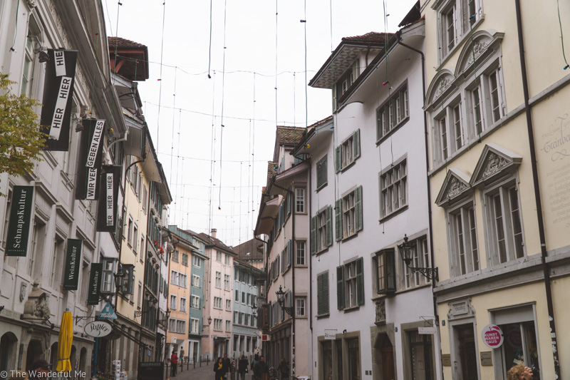 One of Zurich's street with its pastel-colored buildings and twinkling lights strung above the cobblestone road.