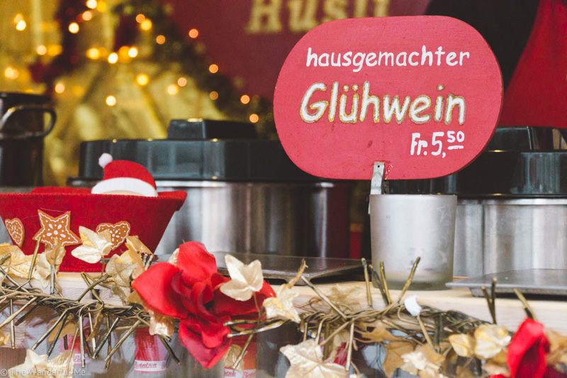 "A sign stating ""Hausgemachter Glühwein"" with large pots of hot wine in the background."