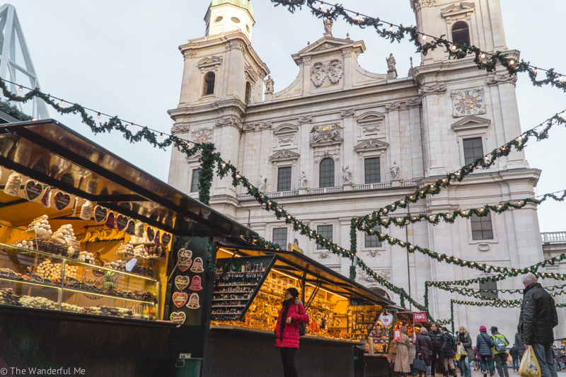 A cathedral in Salzburg in the background with golden lit Christmas Market stands in the foreground.