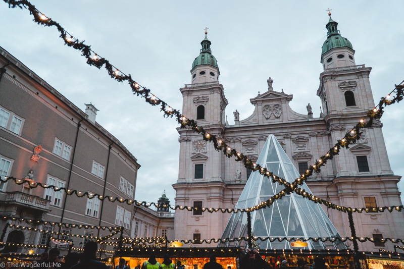 Salzburg Christkindlmarkt in front of the Dom zu Salzburg. Twinkling string lights strung high above the market with the smell of sweet glühwein wafting in the air.