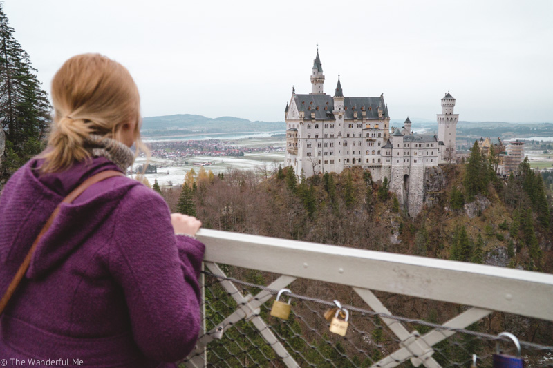 Sophie standing on a bridge admiring the view of Neuschwanstein Castle in the distance.