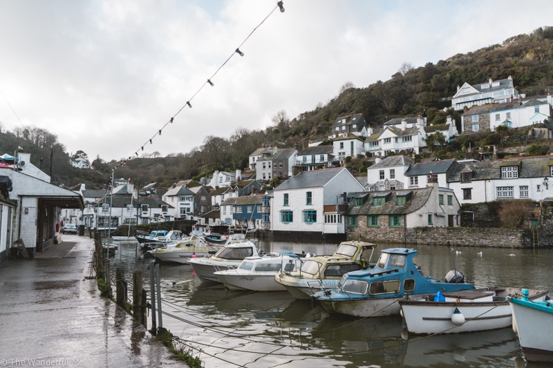 The small seaside village of Polperro and its marina, laden with bobbing fishing boats and small seaside cottages in the background.
