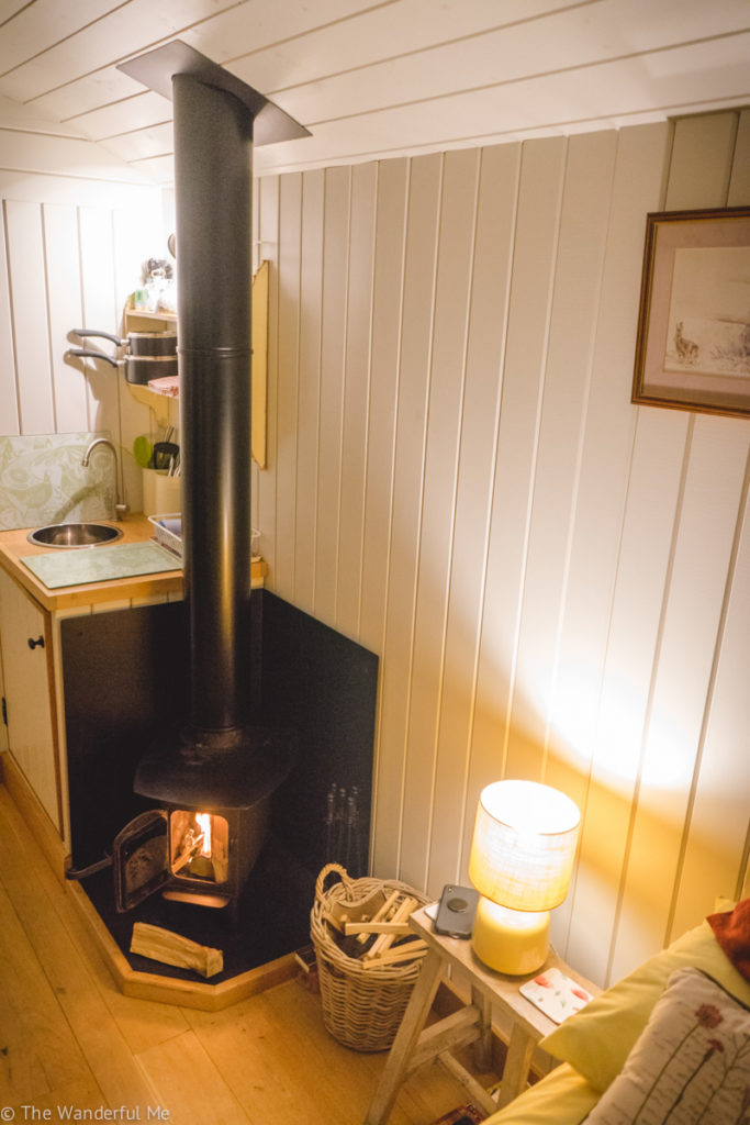 A view of the fireplace and kitchen area in the hut.