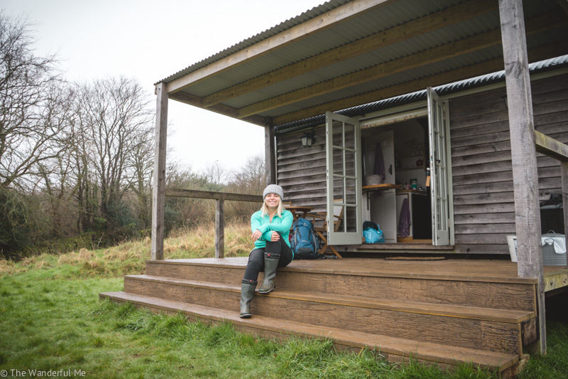 Sophie sitting on the steps of the Shepherd's Hut deck.