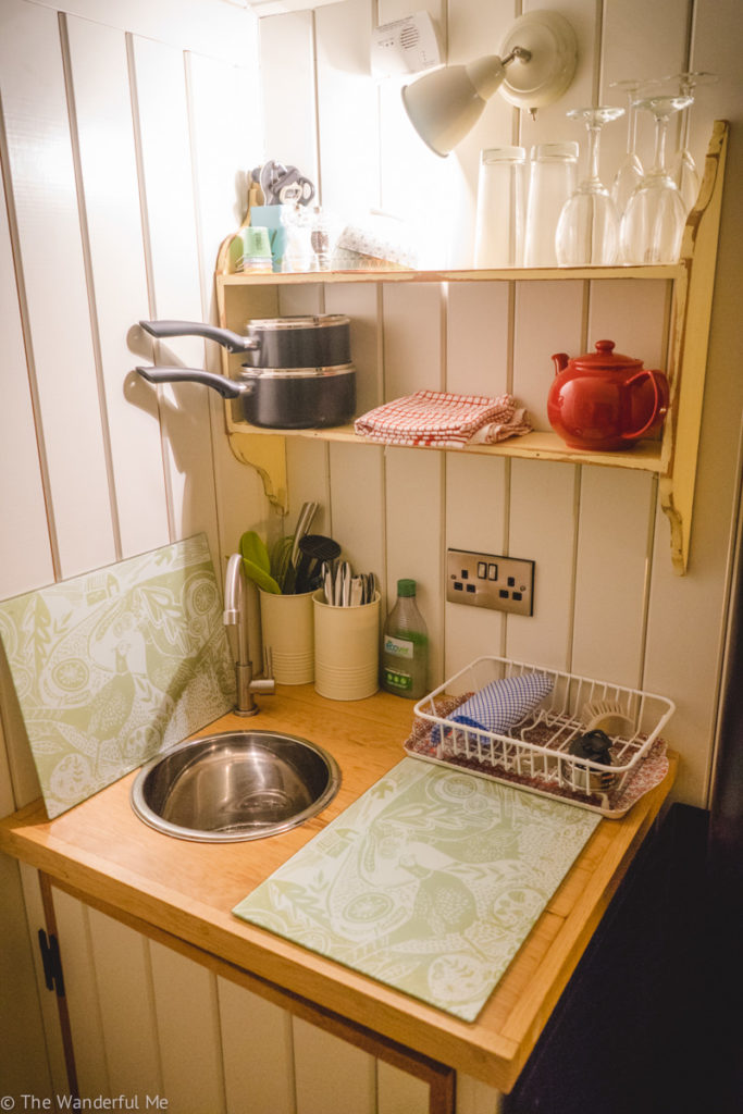 Pots, glasses, and a little red teacup are situated on shelves in the kitchen area. There's also the small sink and cutting board on the countertop.