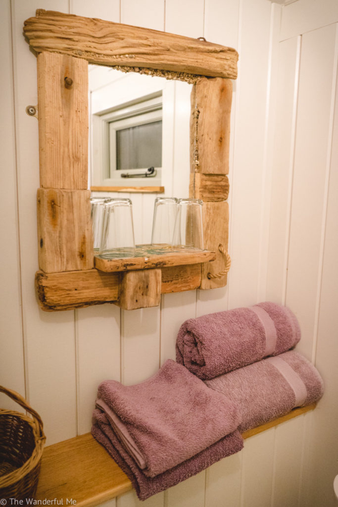 Pink towels situated on a small shelf are for guests in the bathroom, as well as a mirror on the wall.