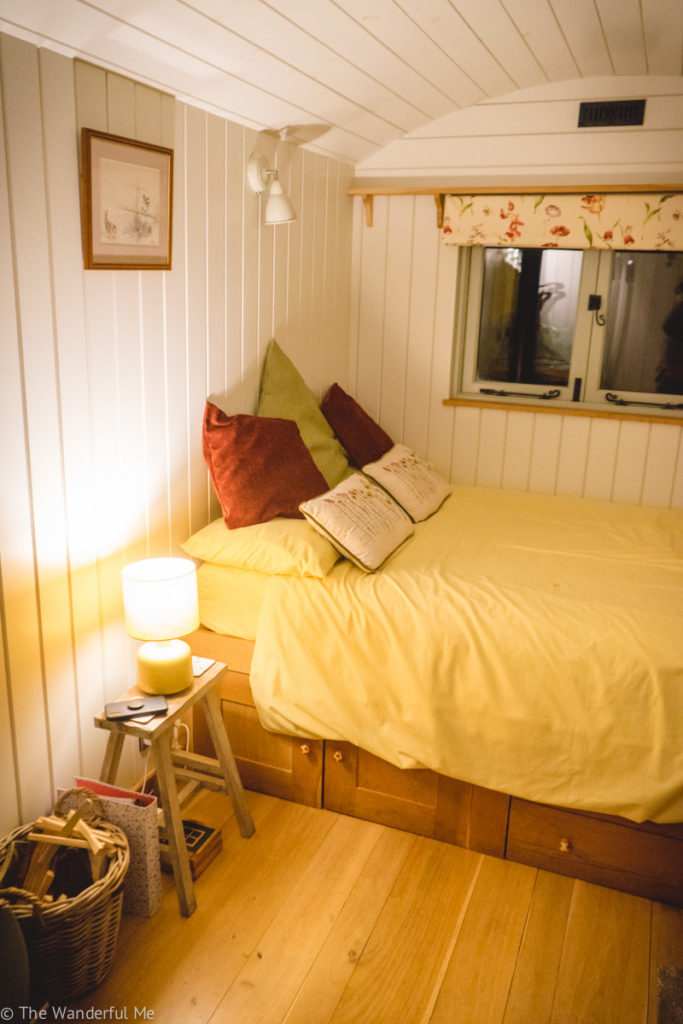 The hut's bed, bedside table and lamp. All looking rather cozy.