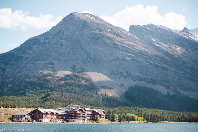 Many Glacier Hotel at the base of a mountain and on the shores of Swiftcurrent Lake.