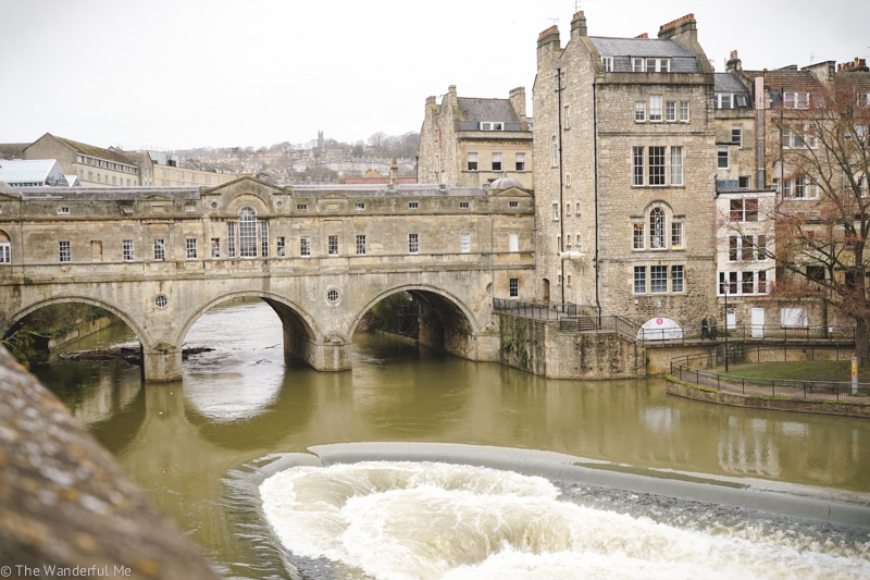 Pulteney Bridge, the flowing River Avon, and the river's weir, making a U-shaped barrier in the water flow.