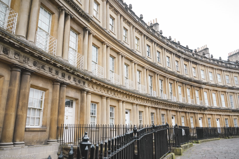 The black fence circling around with the crescent shape of the Royal Crescent.