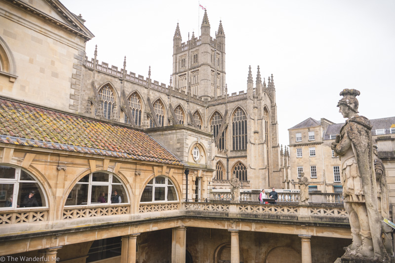 A view from the upper walkway at The Roman Baths in Bath, England, where you can see a statue and Bath Abbey in the background.