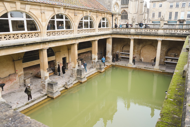 Looking down below at the main bath with its murky green waters and moss-covered stone in The Roman Baths from the upper walkway.