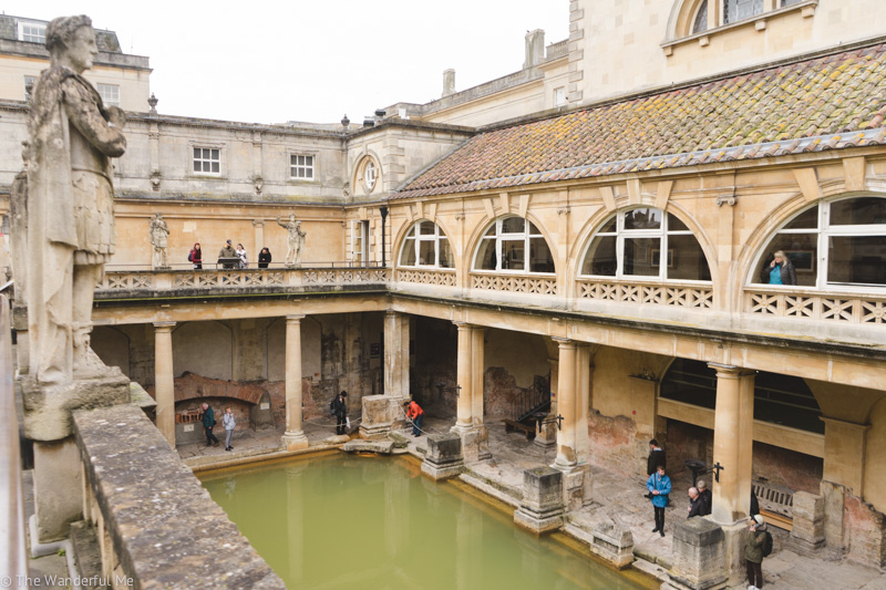 Another viewpoint from the upper walkway at The Roman Baths looking at the bath below and people admiring the historic site.
