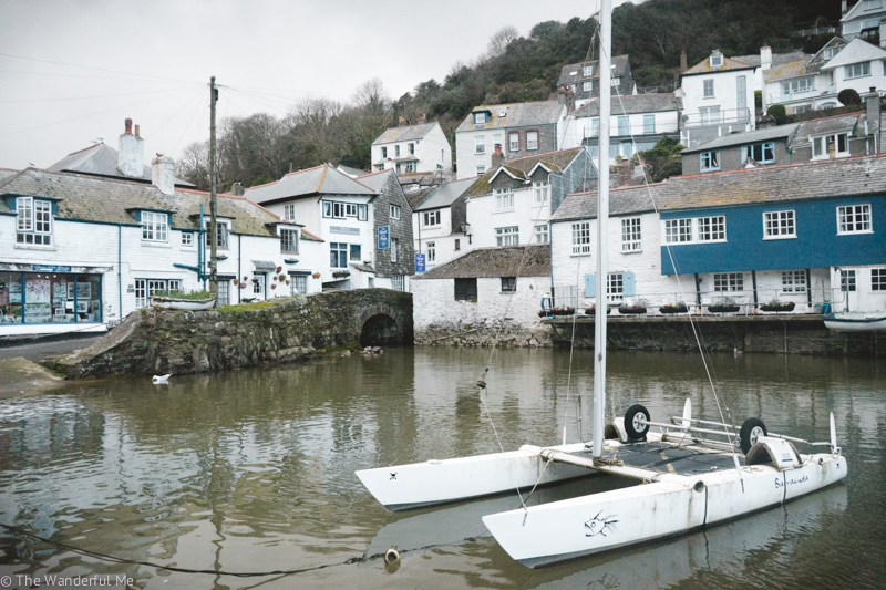 A lonely sailboat floats in the Polperro harbor with beautiful blue and white buildings in the background.