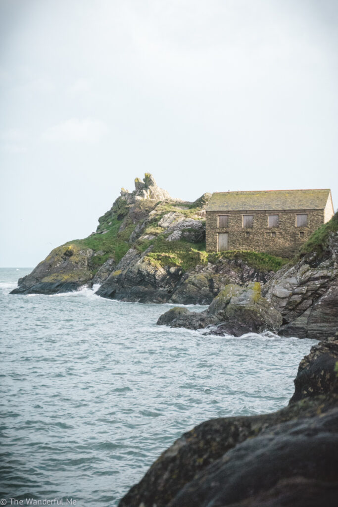 Overlooking the view from the Polperro harbor, which is of an abandoned building on the jagged rocks.