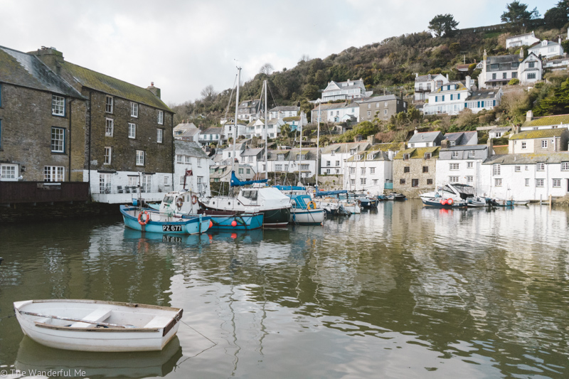 A view of the Polperro harbor, which is filled with both small and large fishing boats, as well as a view of the Polperro hillside, where cottages and homes hug the sides.