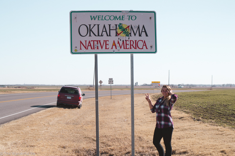 """Sophie standing in front of a sign that says, """"Welcome to Oklahoma, Native America."""" The road tripping van in is the background!"""
