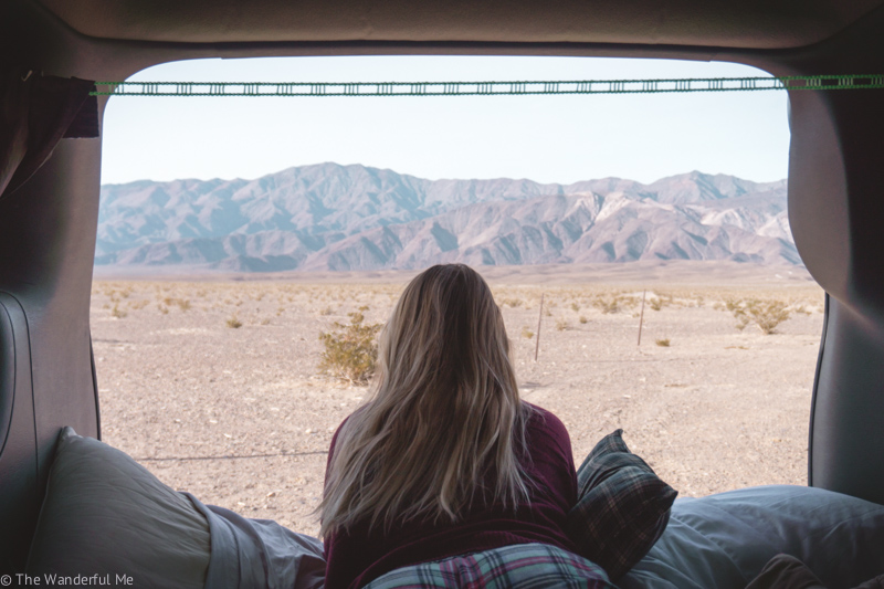 Sophie laying in the back of the Town and Country road trip van, looking out at the marvelous Death Valley landscape. Not another person in site! Which is why RV-ing and road tripping is a great way to social distance and travel.